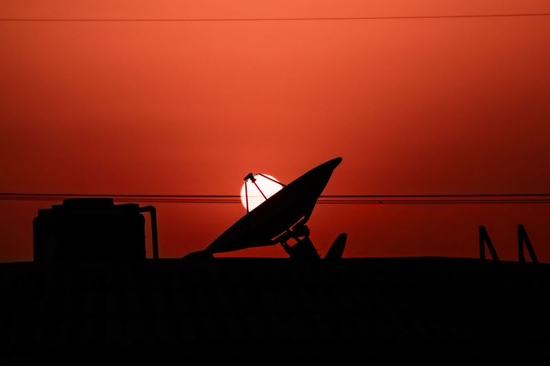 Silhouette satellite dish on building terrace against orange sky