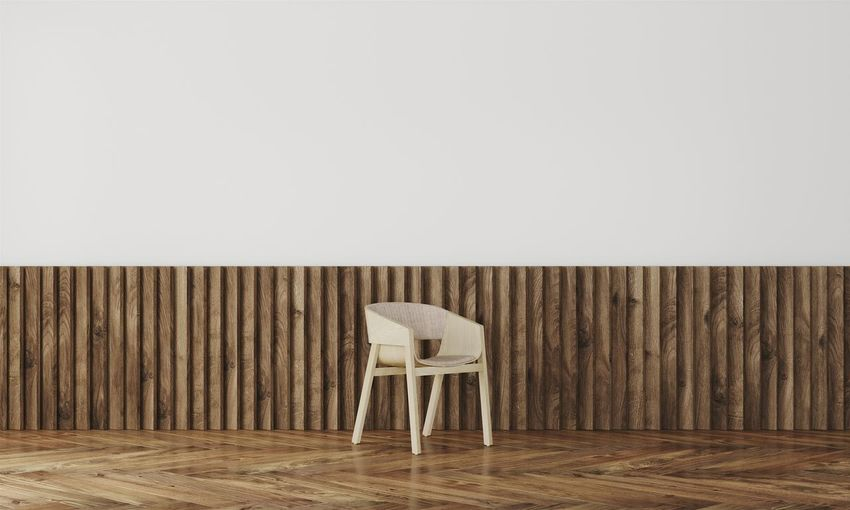 Empty chair on hardwood floor against wall at home