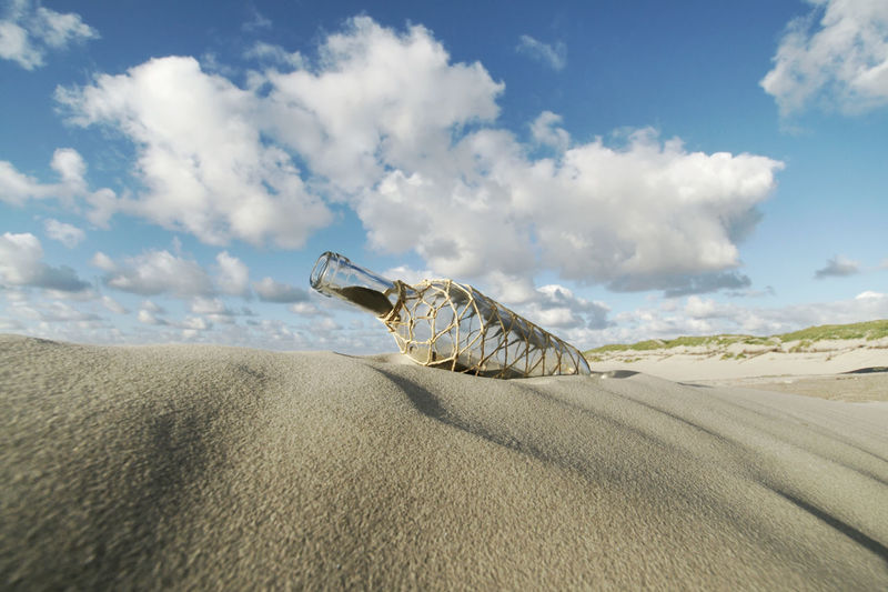 Abandoned Bottle On Sand At Beach Against Sky