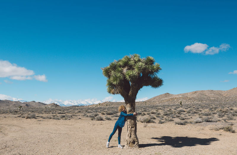 Woman hugging tree in desert against blue sky