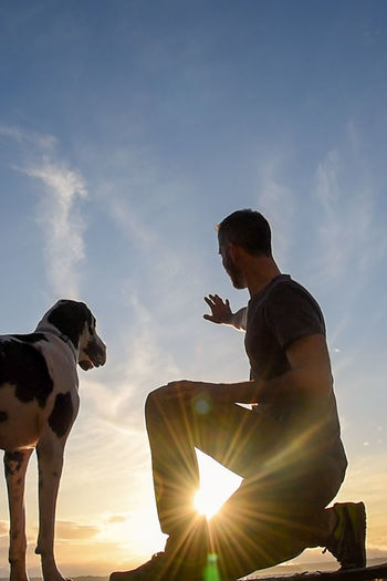Low angle view of man and dog against sky