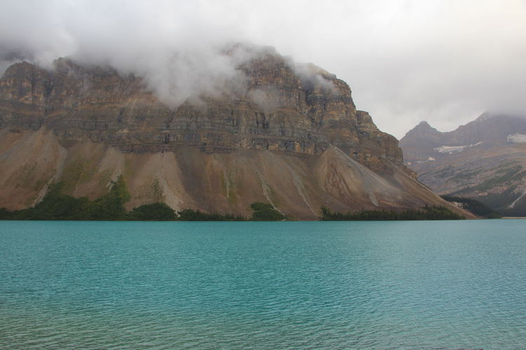Bow Lake Water Scenics - Nature Mountain Beauty In Nature Waterfront Tranquil Scene Tranquility Nature Sky No People Non-urban Scene Lake Day Mountain Range Idyllic Rock Cloud - Sky Travel Destinations Outdoors Formation Eroded View Into Land Turquoise Colored