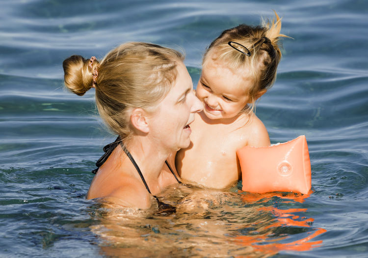 Smiling woman with daughter in sea