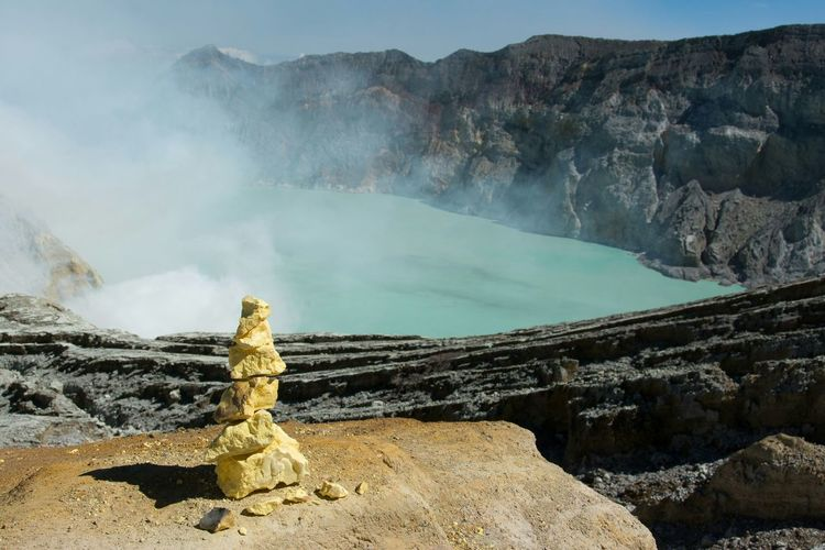 Rock Stack Against Smoke Emitting From Hot Springs At Ijen