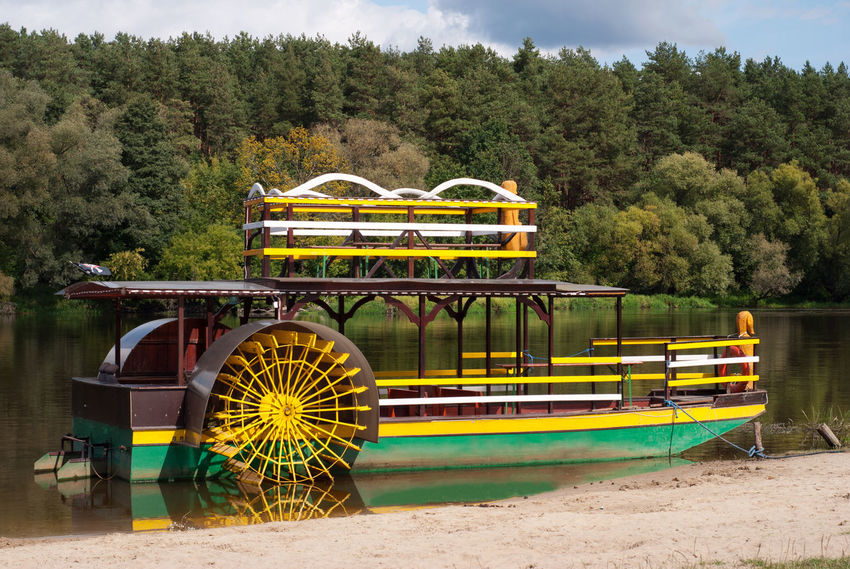 Sternwheeler moored on river strand attraction waiting for tourists, yellow-green old paddle wheeler, steamer or steamboat-like riverboat named Katamaran on Bug River in Serpelice, Poland, woods behind. Horizontal orientation, nobody. Polish tylnokolowiec, parostatek nazwany Katamaran, imitacja jako turystyczna atrakcja na rzece Bug w Serpelicach. Boat Coast Green Imitation Katamaran Moored No People Old Outdoors Paddle Poland River Riverboat Ship Side-wheeled Steamboat Steamer Steamship Sternwheeler Transportation Tylnokolowiec Water Wheel Wheeler Yellow