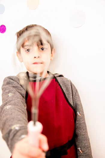 Close-up of boy holding wire whisk