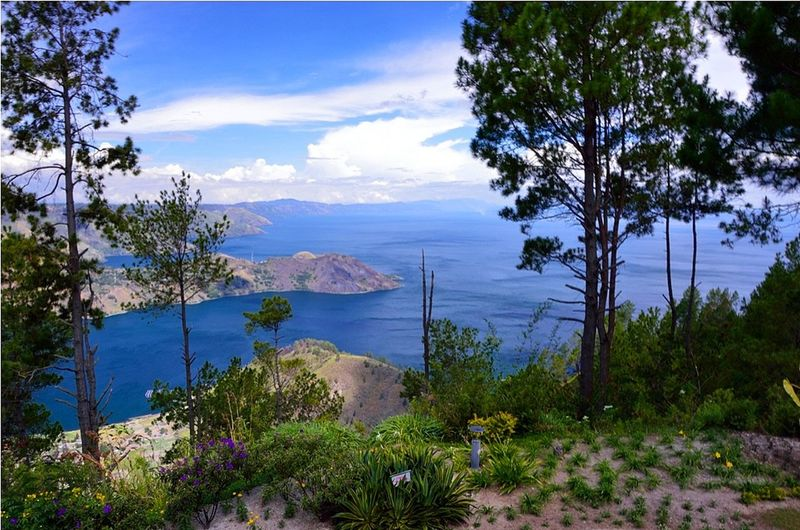 A beautiful view of Lake Toba, taken from tongging point, Taman Simalem Resort, North Sumatera Beauty In Nature Blue Cloud - Sky Danau Toba Distant Flower Green INDONESIA Island Lake Toba Long Exposure Mountain Nature Remote Scenics Sky SUMATERA UTARA Tourism Travel Destinations Tree Vacations Water