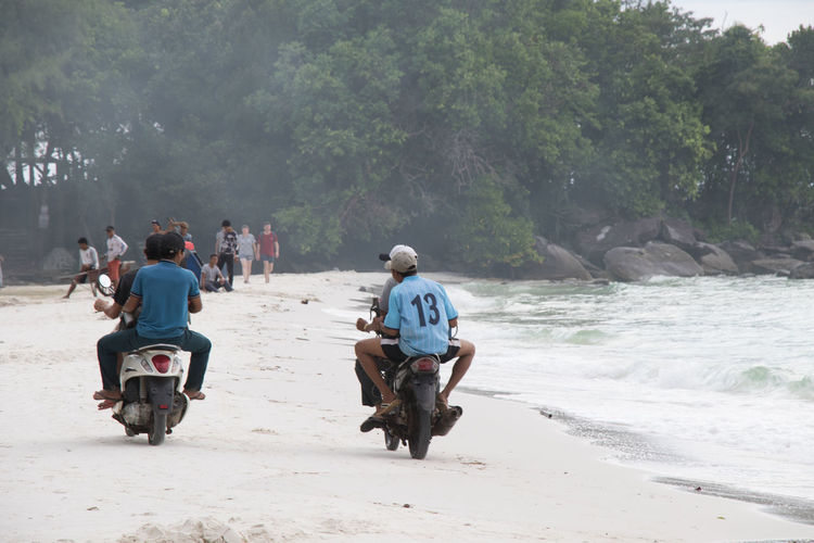 Rear view of people riding motorcycle on road