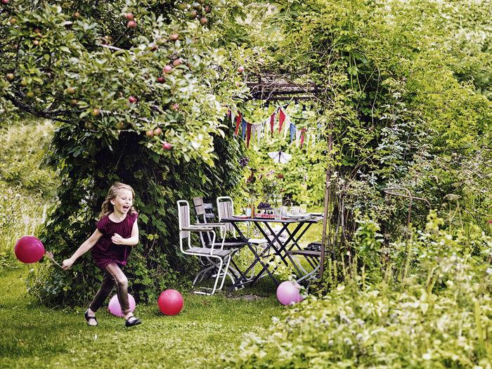 Portrait of girl holding plants in yard