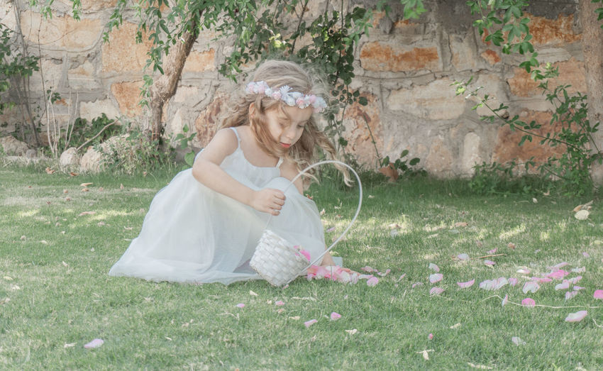Cute Girl Collecting Petals From Grassy Field
