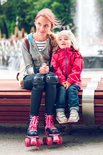 Full Length Of Girl With Sister On Bench Against Fountain At Park