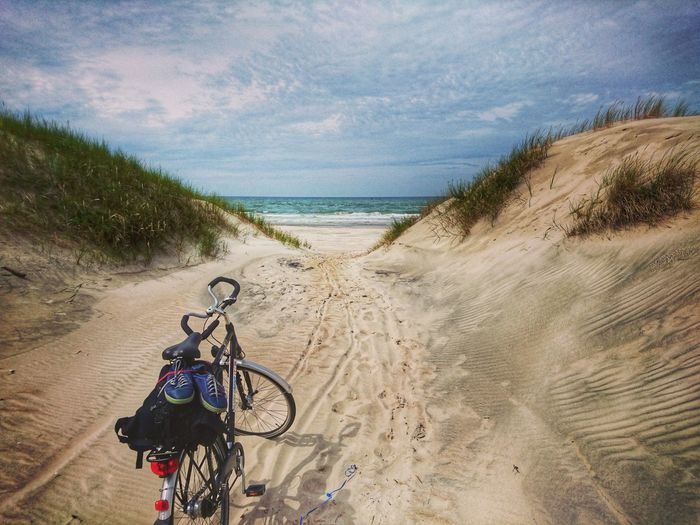 Bicycle parked on footpath at beach