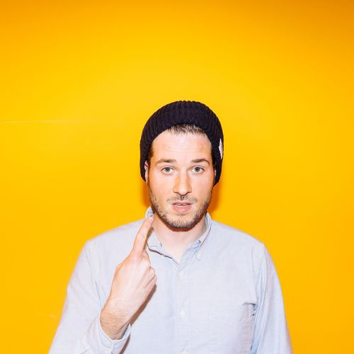Portrait of young man showing index finger against yellow background
