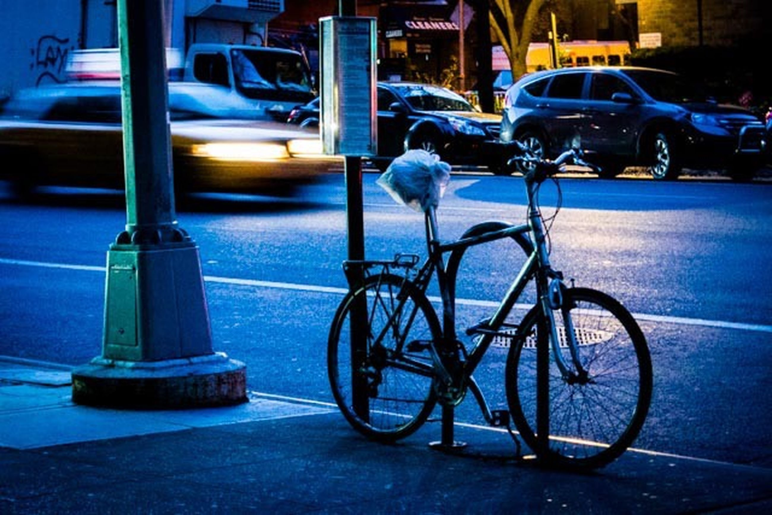 transportation, mode of transport, land vehicle, bicycle, stationary, parked, parking, street, car, building exterior, blue, sidewalk, architecture, built structure, city, parking lot, road, outdoors, no people, travel
