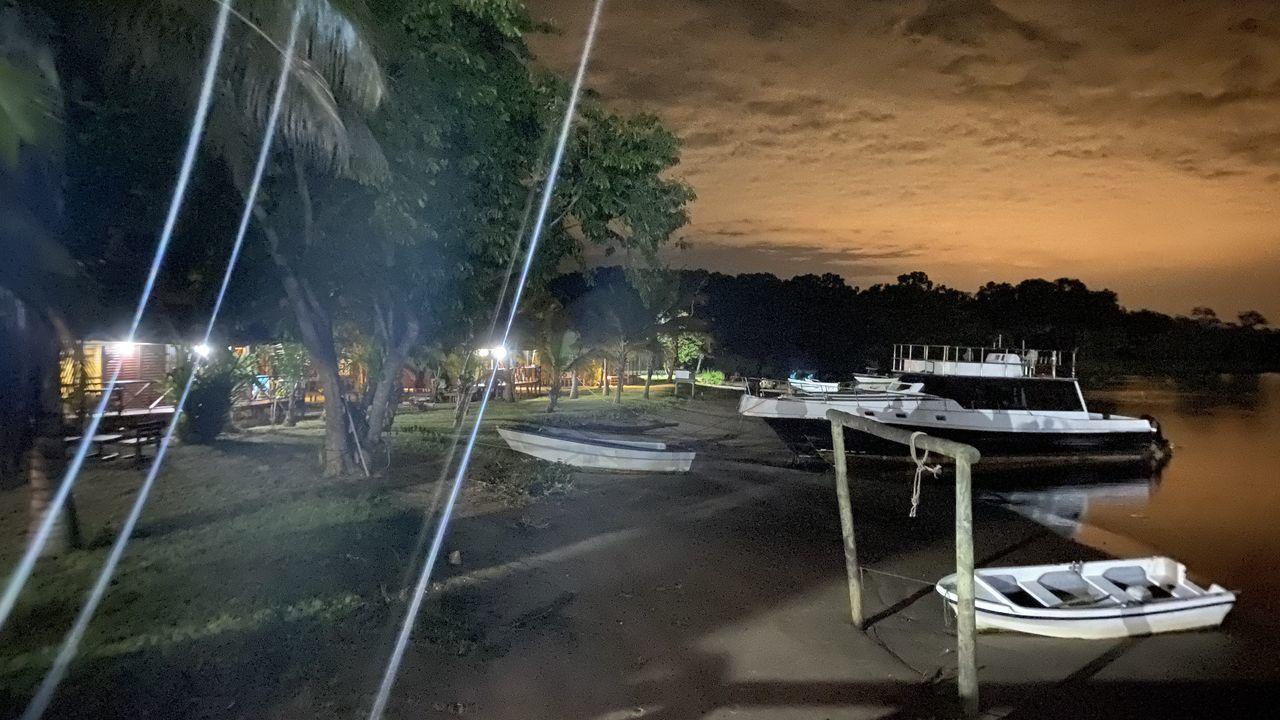 HIGH ANGLE VIEW OF SAILBOATS MOORED ON SEA AT NIGHT