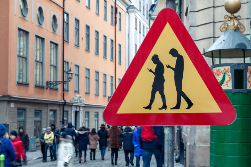 Watch out! Smartphone zombies ahead! Or maybe checking Eyeem?! Architecture Building City Smartphone Young Adult Smartphone Addict Addiction Young Generation Smartphones Distracted Technology Technology Everywhere New Technology Smombies Zombie Stockholm Warning Sign