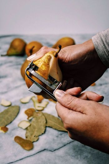 Cropped Image Of Person Peeling Pear On Table