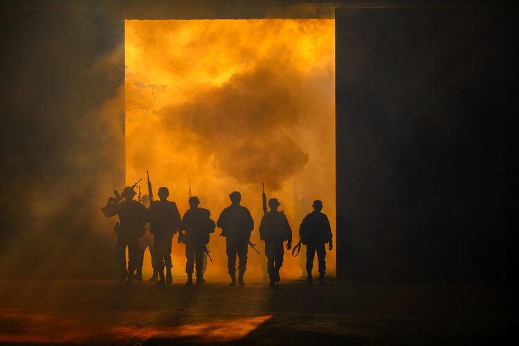 Silhouette soldiers against orange sky