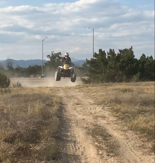4 Wheeler Quad Racing Road Dirt Road Country Road Outdoors Tranquil Scene Vehicle Transportation Day Sky Rear View Having Fun Lifestyles Riding Quads Childhood Innocence Carefree Daughter Jumping Air Shot Catching Air Mid Air Thats My Girl!