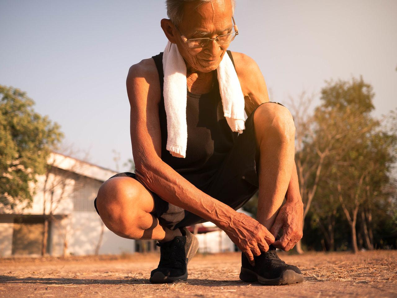 Man tying shoelace while crouching on land against sky