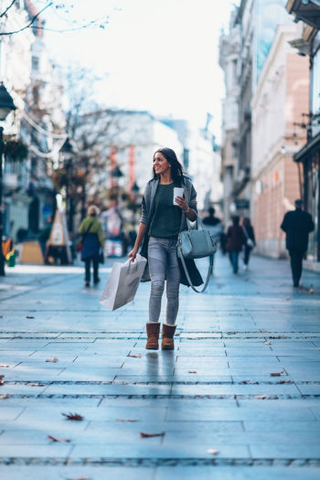 Girl With A Take-Away Coffee In The City Looking Stores And Shopping 20-29 Years 20s Autumn Beautiful City Coffee Dark Hair Lifestyle Shopping Urban City Vertical Composition Woman Young Cute Drink Long Hair Looking One Person Outdoors Shopping Bag Springtime Take Away Coffee Teenager Young Adult