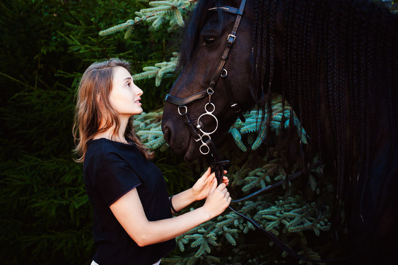 Side view of young woman standing with horse by trees