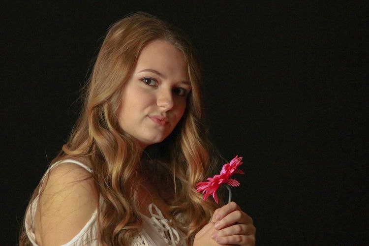 Portrait of beautiful young woman holding flower against black background