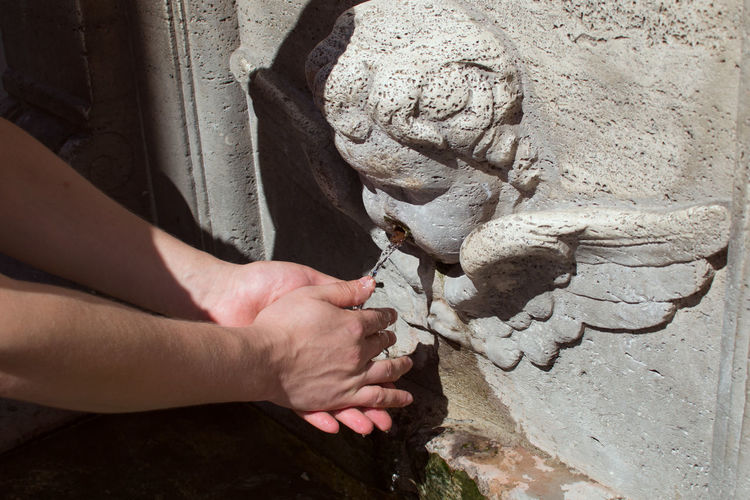Close-up of hands under drinking fountain