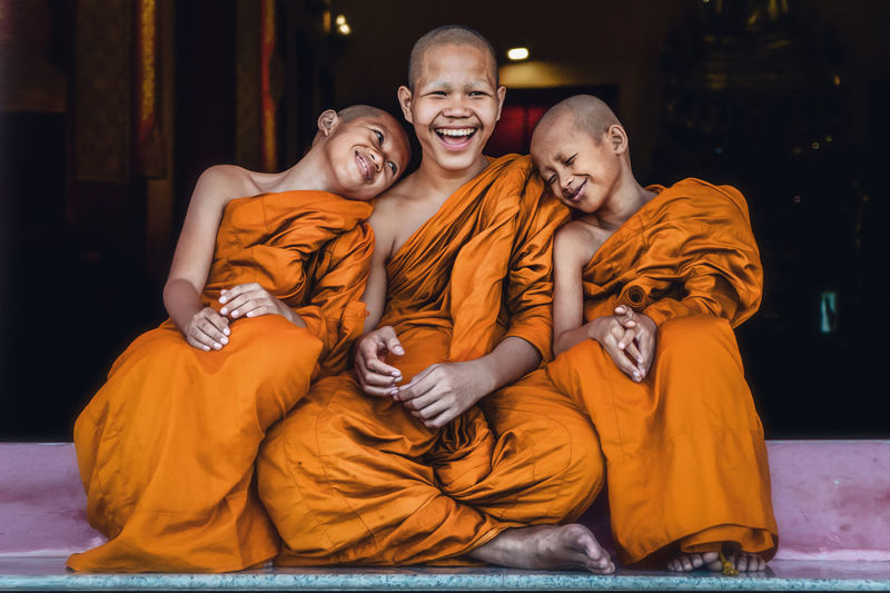 Smiling monks sitting outdoors