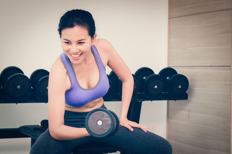 Young woman exercising with dumbbell at gym