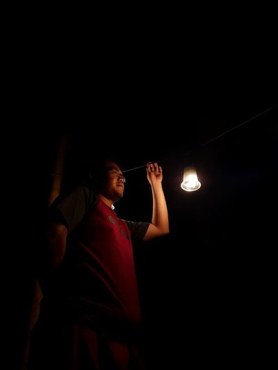 Low angle view of woman standing in illuminated dark