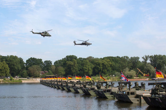 Floating Bridge Air Vehicle Airplane Army Day Flags Flying Helicopter Mid-air Military Military Airplane Military Bridge Military Exercises Mode Of Transport Nature No People Outdoors River Sky Transportation Tree Water