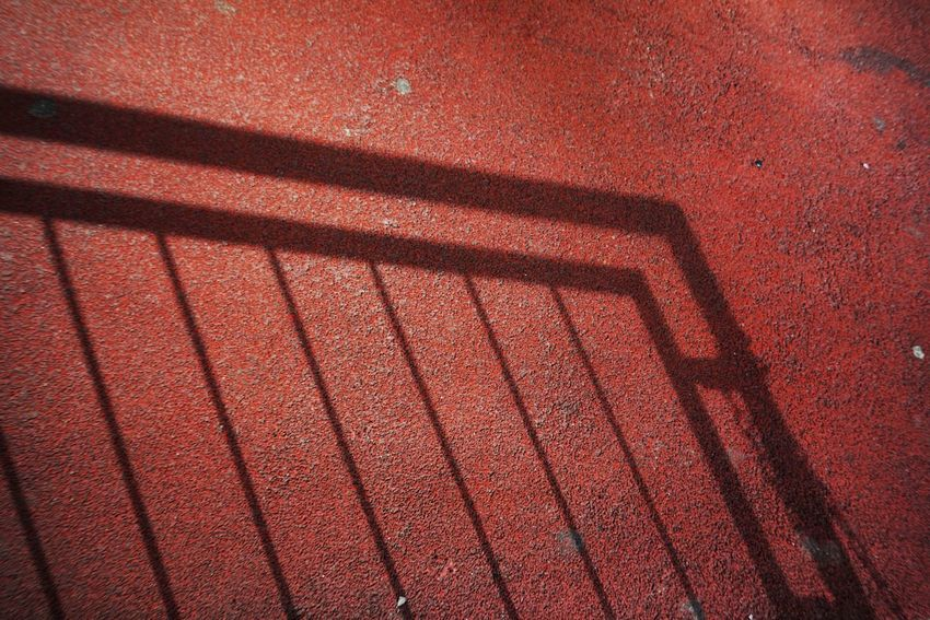Handrail  Red Full Frame No People Backgrounds Pattern Day Shadow Close-up High Angle View Sunlight Outdoors Metal Brown Built Structure Architecture Railing Focus On Shadow