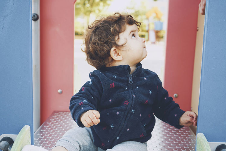 Cute boy looking away while sitting outdoors