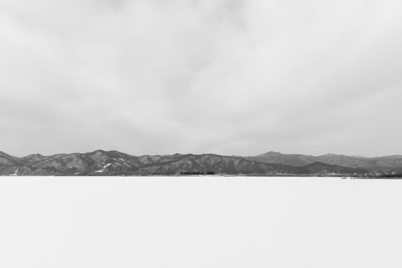black and white image of snow-covered lake, Uiamho Lake in Chuncheon, Gangwondo, South Korea Black & White ChunCheon Cold Lake Cold Weather Gongjicheon Snow Land Uiamho Lake Winter Winter Landscape Beauty In Nature Black And White Blackandwhite Bw Cold Cold Temperature Day Lake Landscape Mountain Mountain Range Nature No People Outdoors Scenics Sky Snow Snow-covered Snow-covered Lake Tranquility Water Winter Lake Winter Land Winter Time