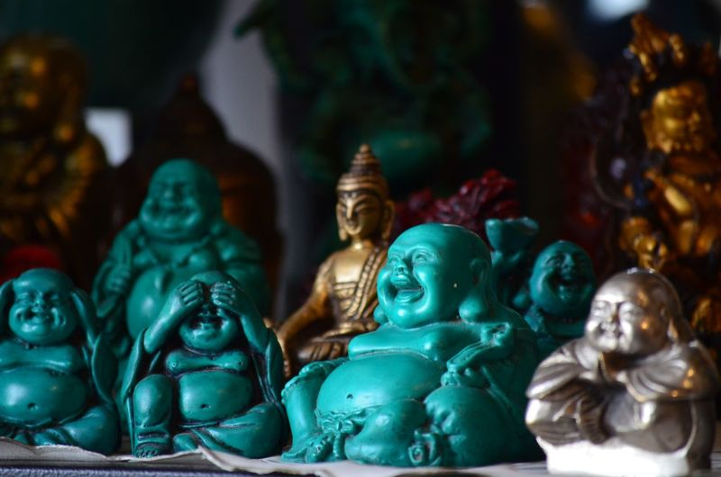 Close-up of laughing buddha statues