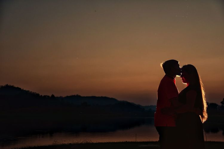 Side View Of Young Couple Kissing At Lakeshore Against Sky During Sunset