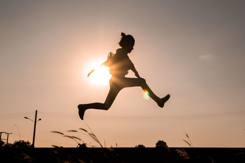 Side view of silhouette woman jumping against sky during sunset