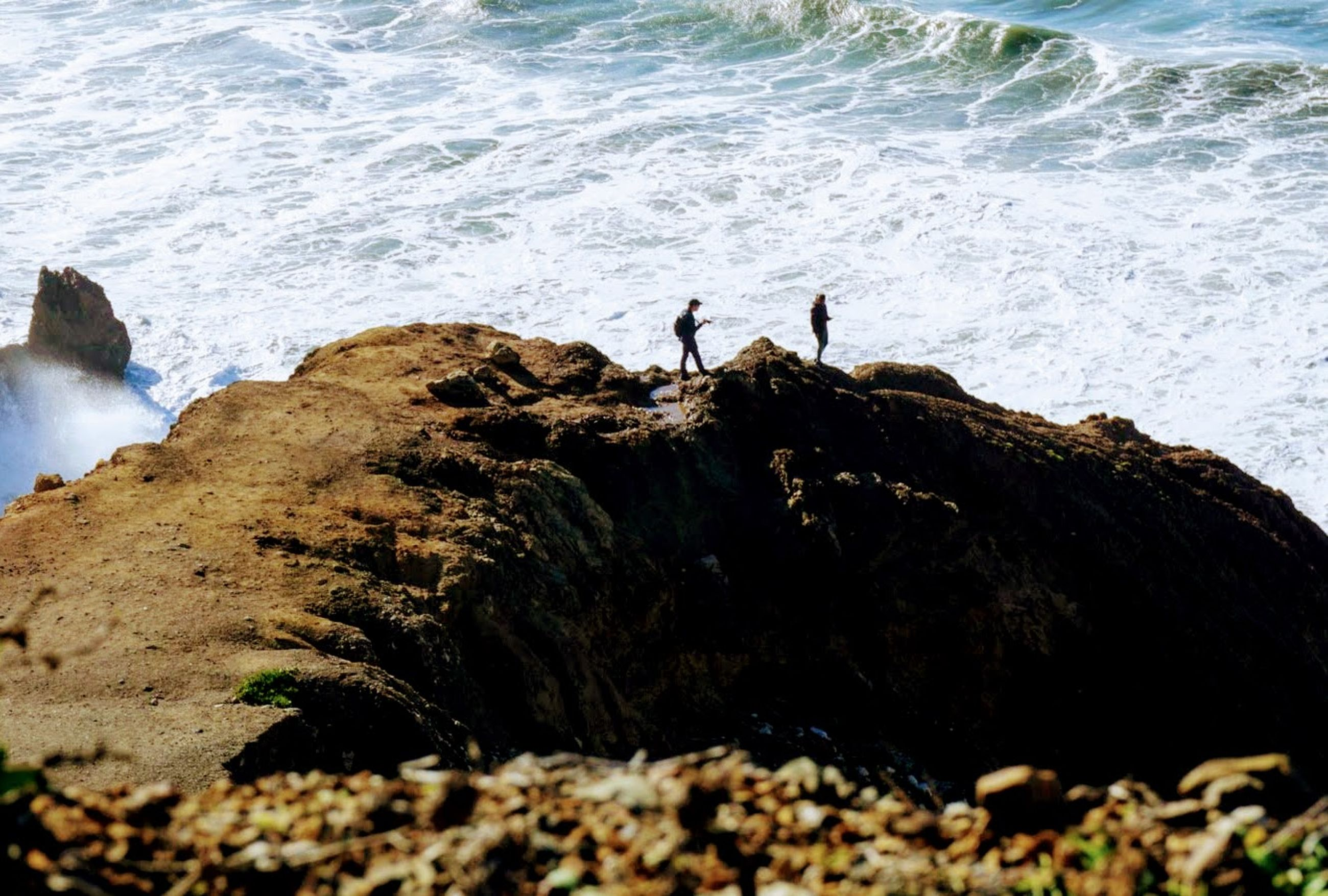 sea, rock, water, rock - object, solid, motion, land, wave, people, beauty in nature, nature, sport, beach, day, two people, aquatic sport, men, surfing, standing, outdoors, looking at view