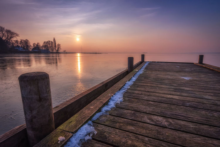 Steg bei Badeinsel am Steinhuder Meer im Winter Water Sky Sunset Tranquil Scene Scenics - Nature Beauty In Nature Tranquility Wood - Material Pier Nature Reflection No People Idyllic Non-urban Scene Jetty Sun Outdoors Wood Paneling Wooden Post Steinhuder Meer Hannover Frozen Lake Horizon Over Water Winter