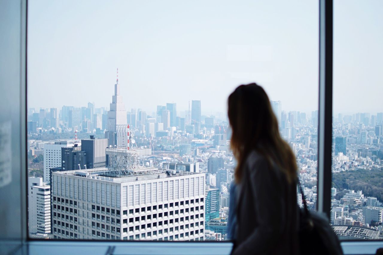 Woman standing by window against cityscape
