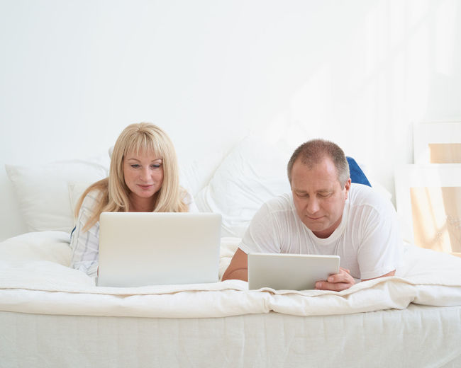 Man and woman using mobile phone while sitting on bed