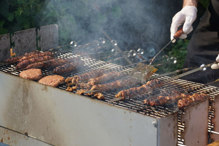 Cropped image of man cooking on barbecue in yard