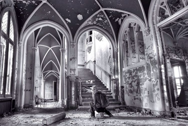 Young Woman Sitting In Abandoned Church