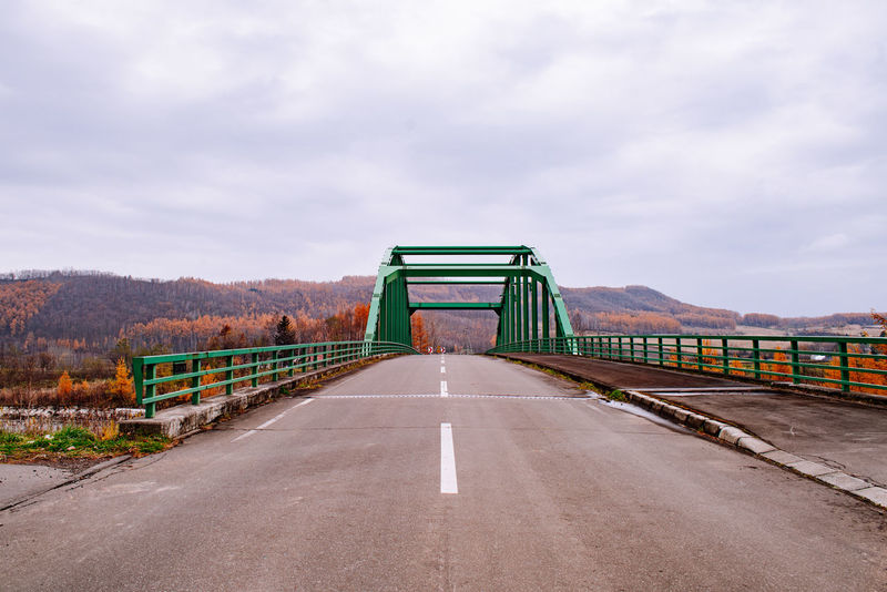 Green bridge towards mountains in Autumn, Biei, Hokkaido, Japan Bridge Road Way Countryside Country Road Autumn Autmn Colors Mountain Range Mountain Travel Transportation Drive Self-driving Trip Tourism Japan Hokkaido Biei Rural Rural Scene Green Sky Copy Space Copy Space In Sky Road Marks