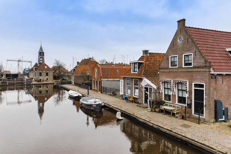 Townscape with old sluice and residential buildings in Hindeloopen, Netherlands. Architecture Cityscape Hindeloopen Netherlands Old Town Row House TOWNSCAPE Boat Brick Building Exterior Built Structure Canal Canals And Waterways Friesland House Nautical Vessel No People Reflection Residential Building Residential District Sluice Town Canal Village Water Waterfront The Architect - 2018 EyeEm Awards