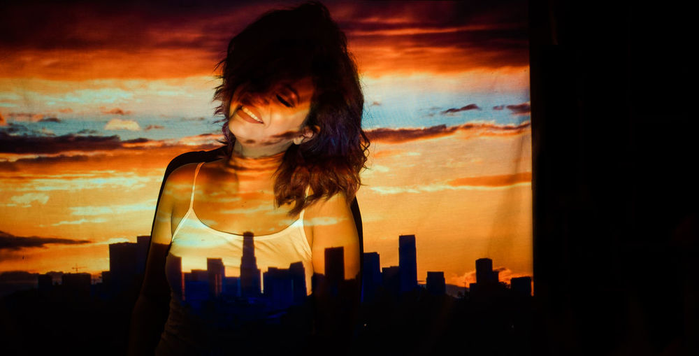 Portrait of woman against cityscape during sunset