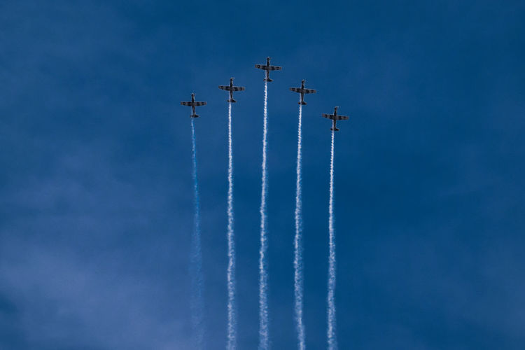 Low angle view of airplanes flying against sky