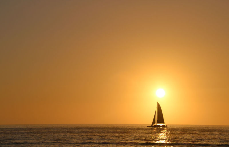 A sailboat came by at just the right time. Beauty In Nature Boat Clear Sky Copy Space Horizon Over Water Nautical Vessel Ocean Orange Color Outdoors Reflection Sailboat Scenics Sea Seascape Sun Sunbeam Sunlight Sunset Tourism Tranquil Scene Tranquility Transportation Travel Water Waterfront