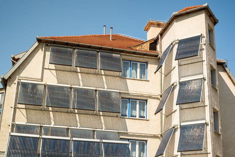 Solar water heating system on a building Solar Water Heating System Architecture Building Exterior Built Structure Building Window Sky Nature Low Angle View Residential District Clear Sky Sunlight Day House Outdoors No People City Blue Roof Town Façade Apartment The Art Of Street Photography My Best Photo